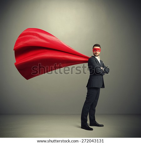 serious businessman dressed as a superhero in red mask and cloak over dark grey background - stock photo