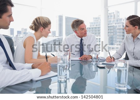 Serious businessman during a meeting talking to his employees in the meeting room - stock photo