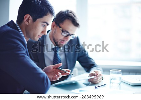 Serious businessman explaining data to his colleague at meeting - stock photo