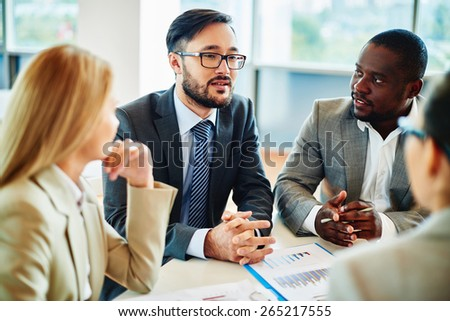 Serious businessman explaining his ideas to managers at meeting - stock photo