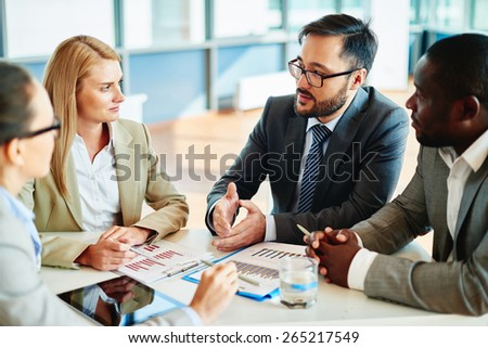 Serious businessman explaining principles of work to his colleagues at meeting - stock photo