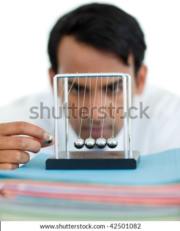 Serious businessman having fun with kinetic balls in the office - stock photo