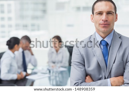 Serious businessman in bright office posing with coworkers on background - stock photo