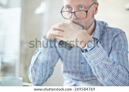 Serious businessman in eyeglasses holding cellphone - stock photo