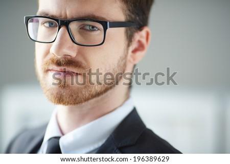 Serious businessman in eyeglasses looking at camera - stock photo