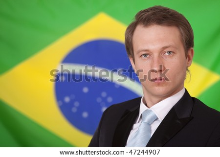 serious businessman in front of brazilian flag - stock photo