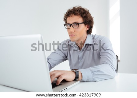 Serious businessman in glasses working on laptop computer in office and looking at camera