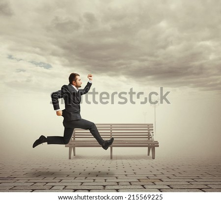 serious businessman in suit running at outdoor against bench