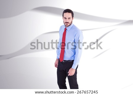 Serious businessman in suit standing against white wave design