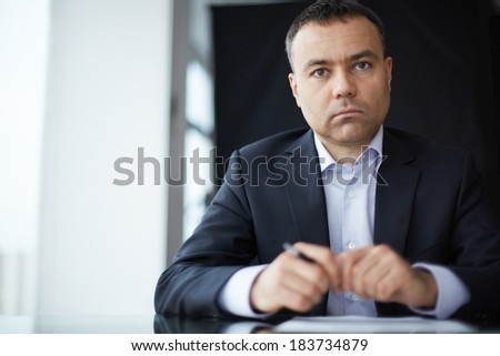 Serious businessman looking at camera at workplace - stock photo