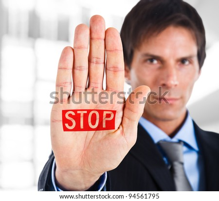 Serious businessman making stop sign - stock photo