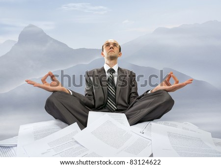 Serious businessman meditating with raised hands in mountains - stock photo