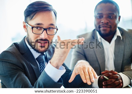 Serious businessman of Asian ethnicity explaining his ideas to colleagues - stock photo