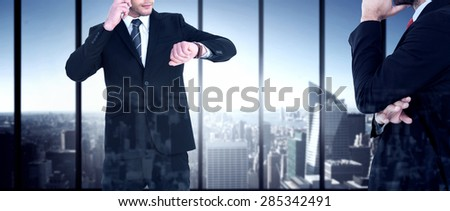 Serious businessman phoning while checking time against room with large window looking on city