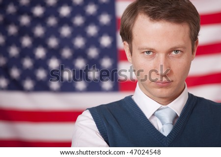 serious businessman posing over american flag - stock photo