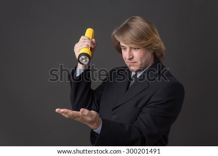 Serious businessman posing with yellow flashlight in his hand. Middle-haired man in black business suit is going to clear up the situation. - stock photo
