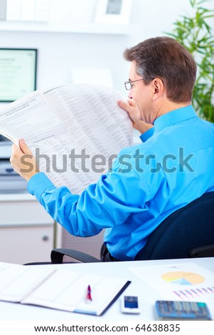 Serious businessman reading newspaper in the office