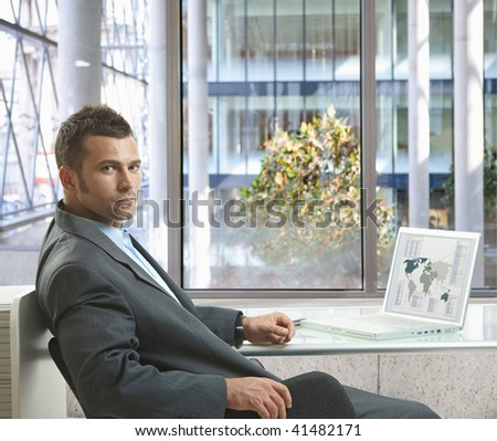 Serious businessman sitting at desk in office, working with laptop computer, looking back. - stock photo