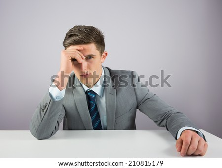 Serious businessman sitting at desk on grey background