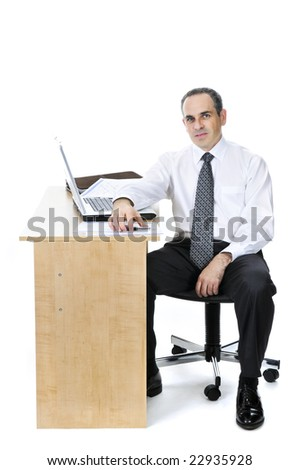 Serious businessman sitting at his desk isolated on white background
