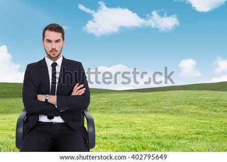 Serious businessman sitting with arms crossed against blue sky over green field