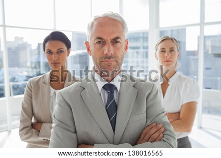Serious businessman standing in front of colleagues with arms crossed - stock photo