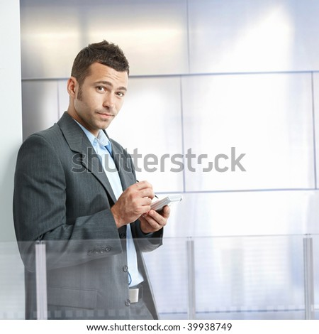 Serious businessman standing in modern office with glass and metal walls, using smart phone. - stock photo
