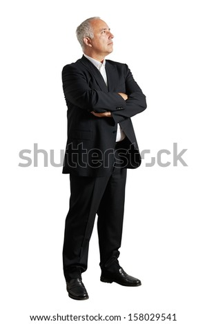 serious businessman standing in the studio and looking up - stock photo