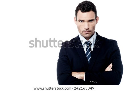 Serious businessman standing with arms folded  - stock photo