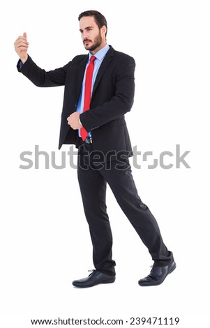 Serious businessman standing with arms raised on white background - stock photo
