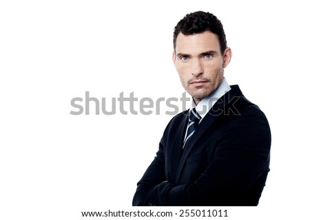 Serious businessman standing with folded arms