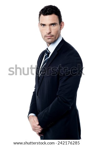 Serious businessman standing with hands clasped