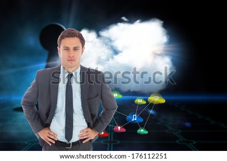 Serious businessman standing with hands on hips against keyhole on technological black background
