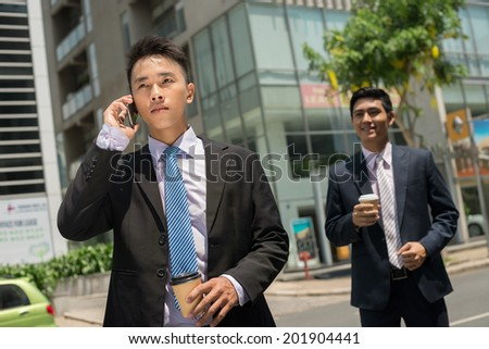 Serious businessman talking on the phone while his colleague waiting for him - stock photo