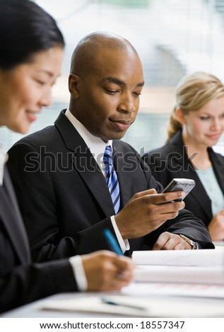 Serious businessman text messaging on cell phone in conference room