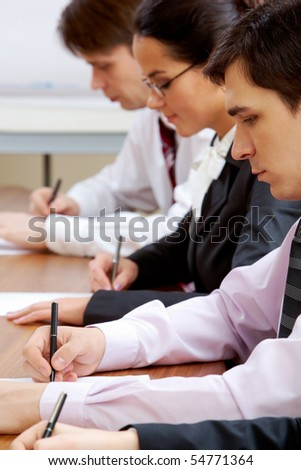Serious businessman thinking during work in row of smart colleagues - stock photo