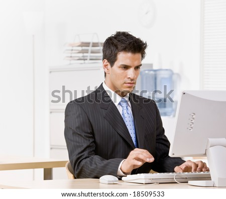 Serious businessman typing on computer - stock photo