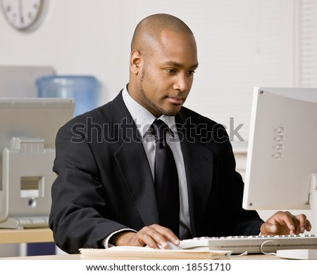 Serious businessman typing on computer at desk