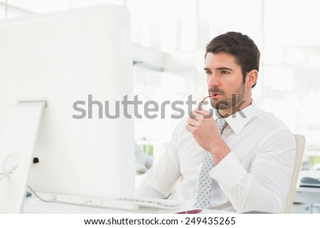 Serious businessman using computer monitor in his office