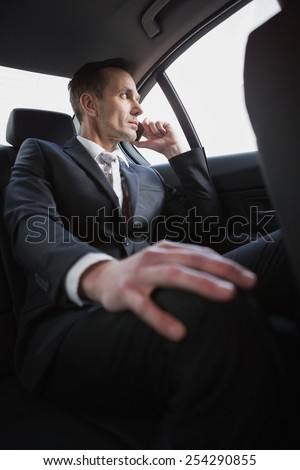 Serious businessman using his phone in his car - stock photo