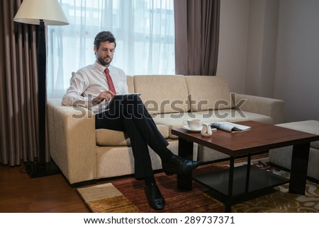 Serious businessman using some application on digital tablet at home
