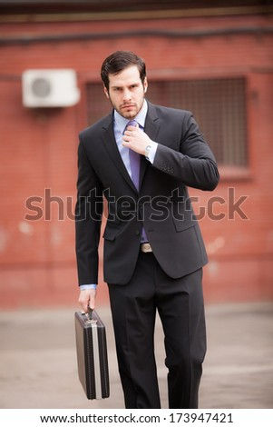 serious businessman walking on the street and fixing his tie - stock photo