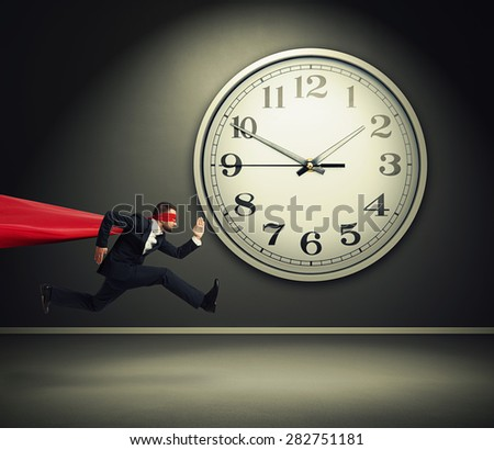 serious businessman wearing like superman running against big white clock in dark room  - stock photo