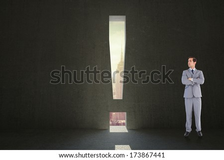 Serious businessman with arms crossed against exclamation mark door in dark room