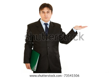 Serious  businessman with folder presenting something on empty hand  isolated on white