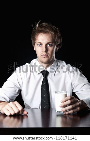 Serious businessman with glass of milk, desaturated with black background - stock photo