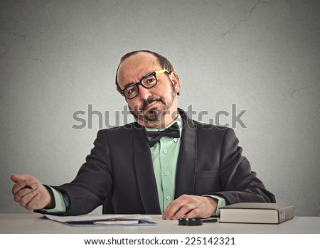 Serious businessman with glasses skeptically looking at you sitting at his desk isolated office grey wall background. Human face expression, body language, attitude, life surrounding perception - stock photo