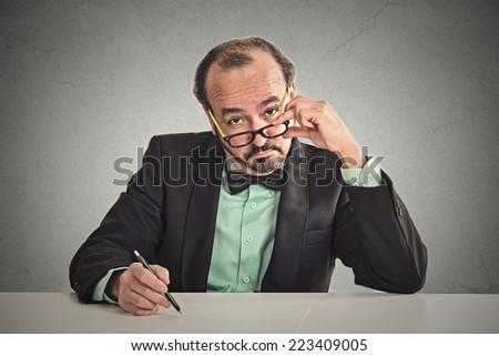 Serious businessman with glasses skeptically looking at you sitting at his desk isolated on office grey wall background. Human face expression, body language, attitude  - stock photo