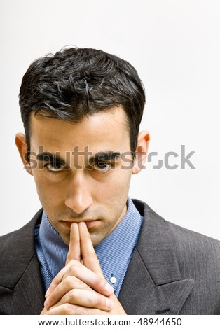 Serious businessman with hands clasped - stock photo