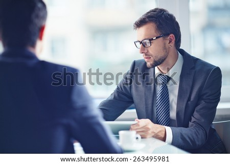 Serious businessman working with touchpad with his colleague near by - stock photo